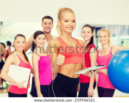 sport, exercise, technology, internet and healthcare - smiling sporty woman with tablet pc computer showing thumbs up - stock photo