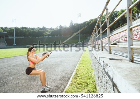 Sport, exercises with training loop outdoors. Profile of girl in rose top and black shorts doing exercises with training loop on stadium. Sporty woman in good shape squatting with training loop