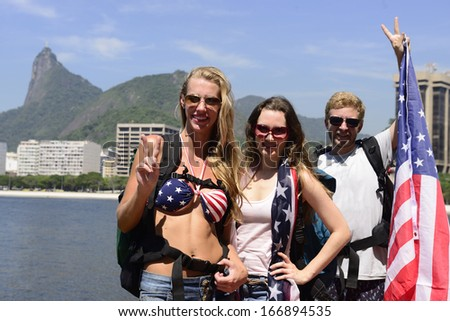 Sport fans holding USA Flag in Rio de Janeiro with Christ the Redeemer in background. - stock photo