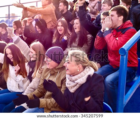 Sport fans wearing hat and scarf clapping and singing on tribunes. Group people. - stock photo