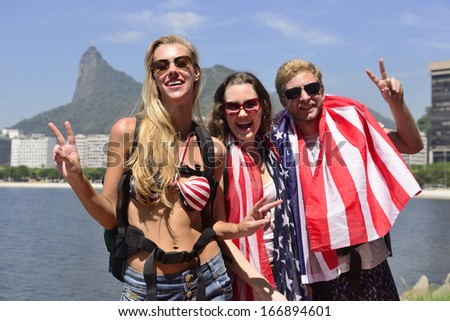 Sport fans with USA Flag in Rio de Janeiro with Christ the Redeemer in background. - stock photo