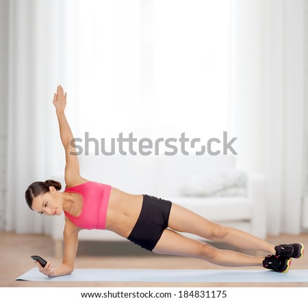sport, fitness and healthcare concept - beautiful asian sporty woman with smartphone doing exercise - stock photo