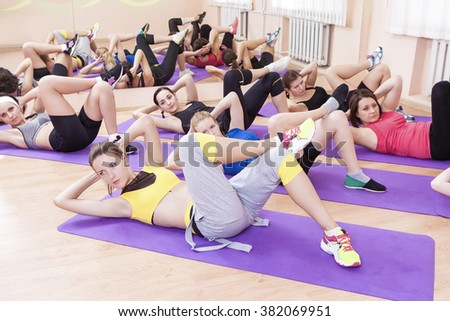 Sport, Fitness and Pilates Concepts. Group of Seven Caucasian Female Athletes Stratching Legs Muscles on Sport Mats. Horizontal Image
