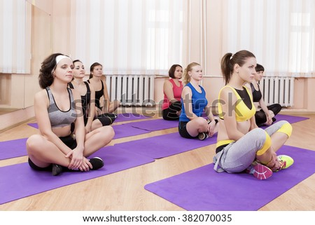 Sport, Fitness and Pilates Concepts. Group of Seven Caucasian Female Athletes Stretching Legs Muscles. Sitting on Sport Mats. Horizontal Image - stock photo