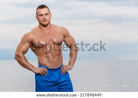 Sport, fitness. Bodybuilder with sexy body on the beach - stock photo