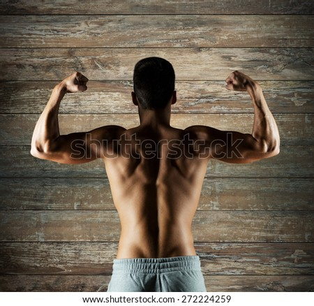 sport, fitness, bodybuilding, strength and people concept - young man or bodybuilder showing biceps over wooden wall background from back - stock photo