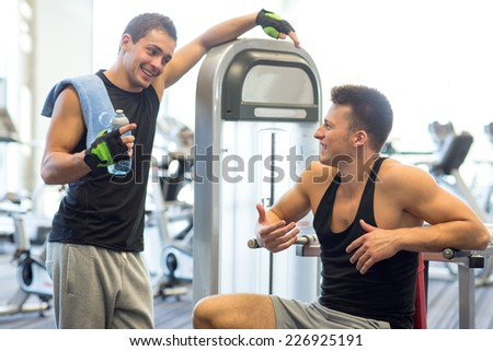 sport, fitness, equipment, lifestyle and people concept - smiling men with bottle of water exercising on gym machine - stock photo