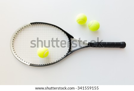 sport, fitness, healthy lifestyle and objects concept - close up of tennis racket with balls - stock photo
