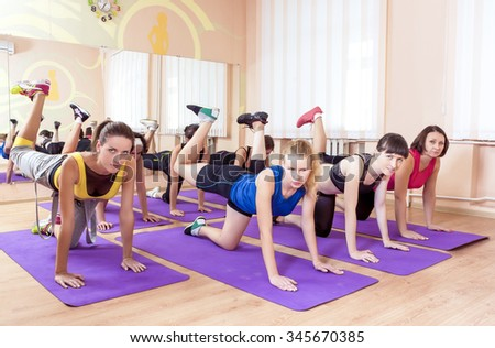 Sport, Fitness, Healthy Lifestyle Concepts. Group of Caucasian Women Having Stretching Workout Indoors on a Purple Sport Mats. Horizontal Image Composition - stock photo