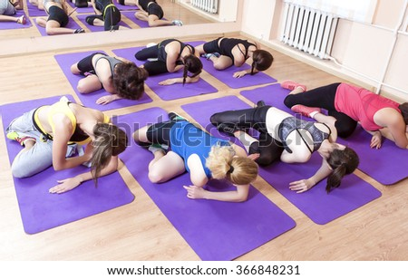 Sport, Fitness, Healthy Lifestyle Concepts. Group of Caucasian Women Having Stretching Workout Indoors on Purple Sport Mats. Horizontal Image Composition  - stock photo