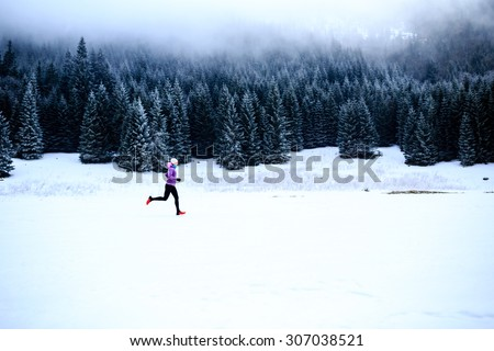 Sport, fitness inspiration and motivation. Young happy woman cross country running in mountains on snow, winter day. Female trail runner jogging exercising outdoors. - stock photo