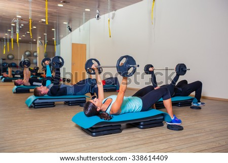 Sport, fitness, lifestyle and people concept - group flexing muscles with barbells in gym.