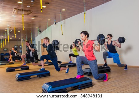 Sport, fitness, lifestyle and people concept - group flexing muscles with barbells in gym. - stock photo