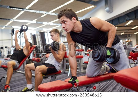 sport, fitness, lifestyle and people concept - group of men flexing muscles with dumbbells in gym - stock photo