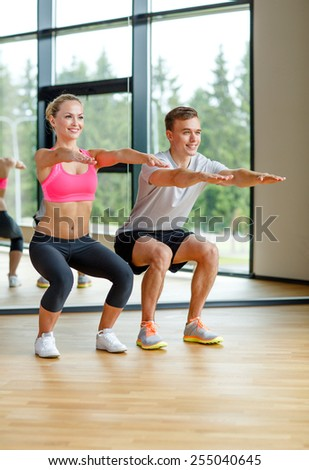 sport, fitness, lifestyle and people concept - smiling man and woman exercising in gym - stock photo