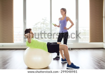 sport, fitness, lifestyle and people concept - smiling man and woman flexing muscles with exercise ball in gym - stock photo