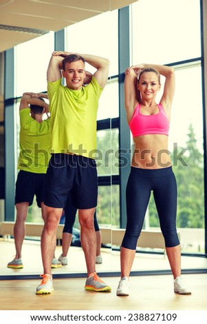 sport, fitness, lifestyle and people concept - smiling man and woman stretching in gym - stock photo