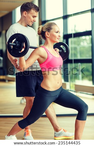 sport, fitness, lifestyle and people concept - smiling man and woman with barbell exercising in gym