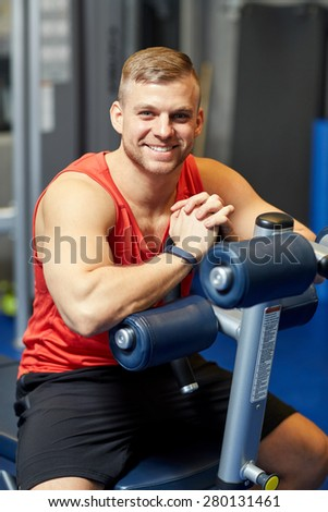 sport, fitness, lifestyle and people concept - smiling man sitting on exercise bench in gym