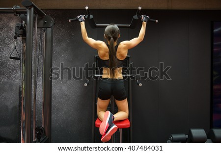 sport, fitness, lifestyle and people concept - woman exercising and doing pull-ups in gym from back