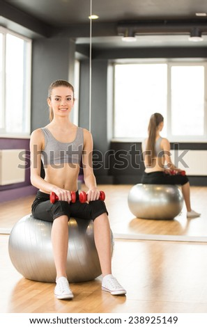 Sport, fitness, lifestyle concept. Smiling woman with exercise ball and dumbbells in gym is looking at the camera. - stock photo
