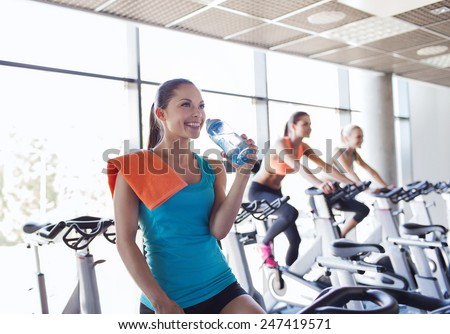 sport, fitness, lifestyle, equipment and people concept - group of women with water bottle riding on exercise bike in gym - stock photo
