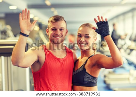 sport, fitness, lifestyle, gesture and people concept - smiling man and woman waving hands in gym - stock photo
