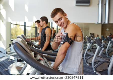 sport, fitness, lifestyle, technology and people concept - man with smartphone and earphones exercising on treadmill in gym