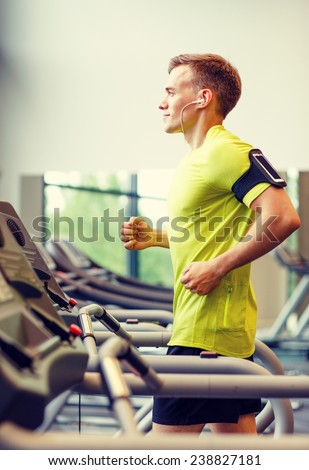 sport, fitness, lifestyle, technology and people concept - smiling man with smartphone and earphones exercising on treadmill in gym - stock photo