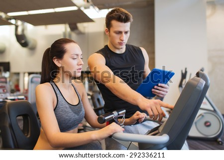 sport, fitness, lifestyle, technology and people concept - woman with trainer working out on exercise bike in gym - stock photo