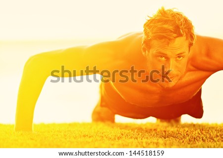 Sport fitness man push-ups. Male athlete exercising push up outside in sunny sunshine. Fit shirtless male fitness model in crossfit exercise outdoors. Healthy lifestyle concept. - stock photo