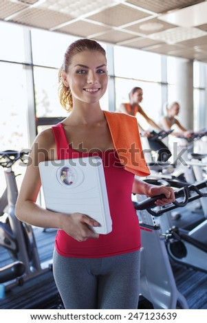 sport, fitness, slimming and people concept - smiling woman with scales and towel in gym - stock photo