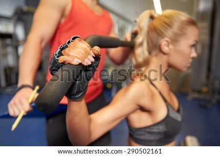 sport, fitness, teamwork and people concept - close up of young woman and personal trainer flexing muscles on cable gym machine - stock photo