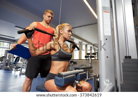 sport, fitness, teamwork and people concept - young woman and personal trainer flexing muscles on cable gym machine - stock photo
