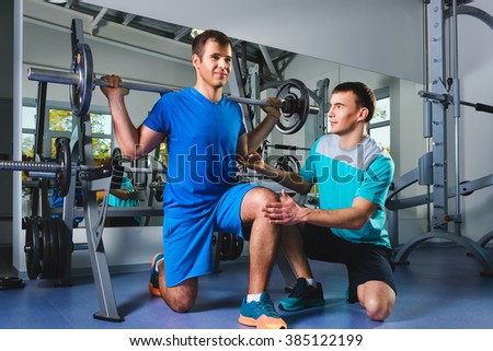 sport, fitness, teamwork, bodybuilding people concept - man and personal trainer with barbell flexing muscles in gym - stock photo