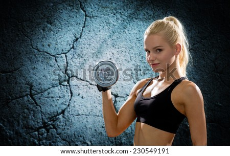 sport, fitness, training, weightlifting and people concept - young sporty woman with dumbbell flexing biceps over concrete wall background - stock photo