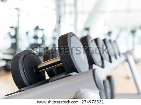sport, fitness, weightlifting and health care concept - close up of dumbbells in gym