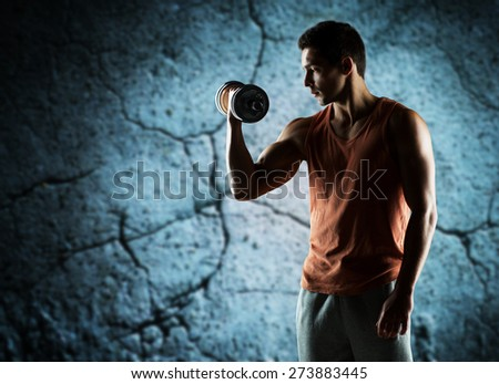 sport, fitness, weightlifting, bodybuilding and people concept - young man with dumbbell flexing biceps over concrete wall background - stock photo