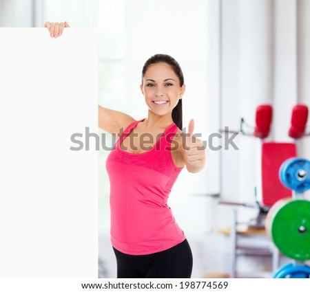 sport fitness woman hold blank board advertisement with empty copy space, young healthy smile girl athletic muscle body, perfect figure show thumb up gesture - stock photo