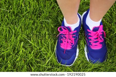 Sport Footwear on Female Feet on Green Grass. Closeup Running Shoes.  - stock photo