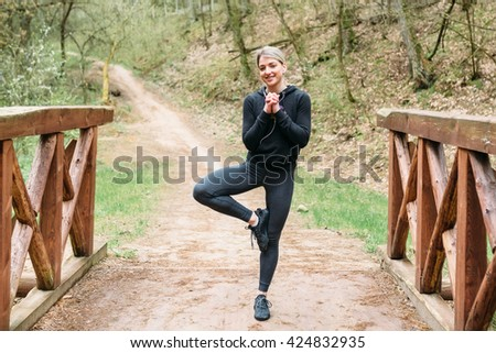 Sport girl doing a workout for a jog in the forest in the sports fotme dark colors and listening to music
