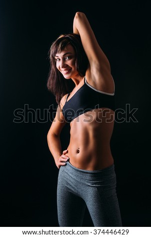 Sport girl doing stretching on a black background