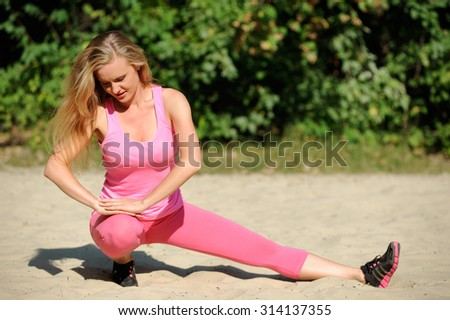 Sport girl is doing exercises on sand