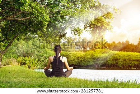 Sport girl meditating in nature green park at the sunrise - stock photo