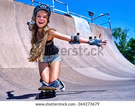 Sport girl rides his skateboard outdoor. - stock photo