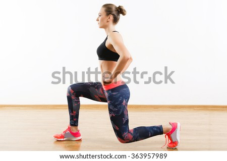 Sport girl with dark hair wearing pink snickers, dark leggings and black short top doing lunge at gym, fitness, white wall and wooden floor, copy space. - stock photo