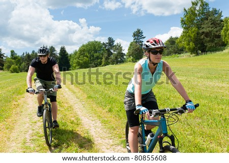 Sport happy couple riding bicycles in countryside meadows - stock photo