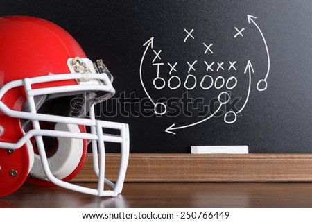 Sport Helmet In Front Of A Chalkboard With Football Play Strategy - stock photo