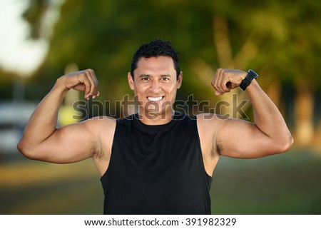 sport hispanic man showing muscles on green park
