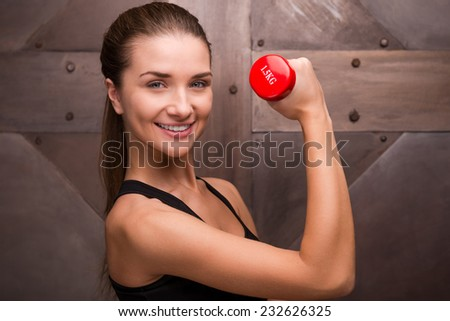 Sport is part of her life. Muscular woman holding dumbbell and smiling while standing against metal background  - stock photo